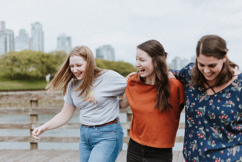 Three women laughing outside