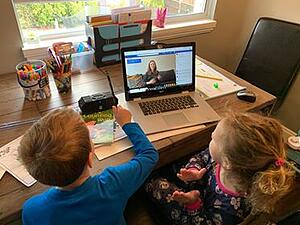 Two young children participating in Virtual Storytime through on a laptop. The storytime is hosted by Vancouver Public Library.